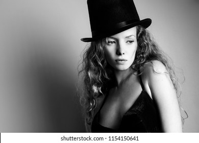 Portrait of beautiful curly girl in a black hat
