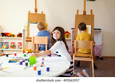 Portrait of beautiful curly girl painting a picture in art class, shallow depth of field