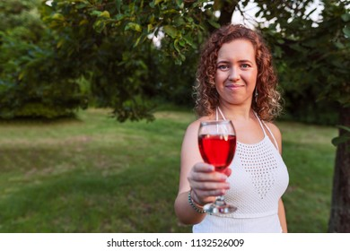 Portrait of a beautiful curly woman holding a glass of wine and offer by a glass of wine