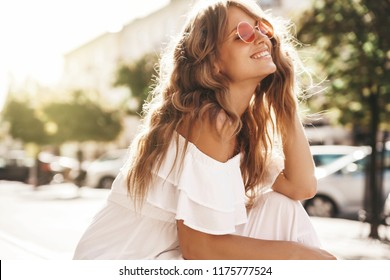 Portrait of beautiful cute blond model with no makeup in summer hipster white dress clothes sitting on the street background