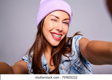 Portrait of beautiful cute brunette woman model in casual summer jeans clothes with no makeup in purple beanie making selfie photo on smartphone isolated on gray