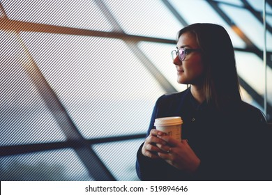 Portrait of beautiful cute hipster girl sitting near with take away coffee in airport. Young female thoughtful look into the window. Copy space for you text message or advertising content