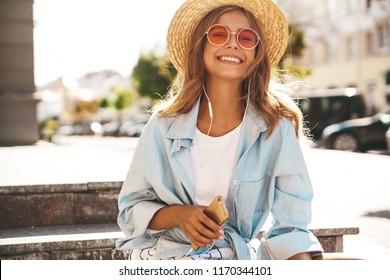 Portrait of beautiful cute smiling blond teenager model in summer hipster clothes sitting on the street background and listening music on her mobile phone