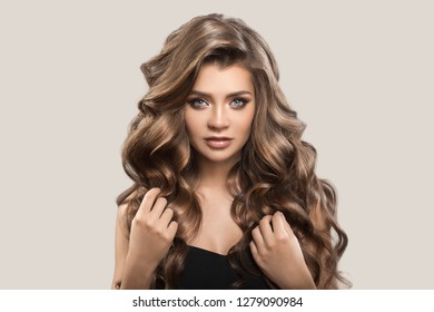 Portrait of beautiful cute woman with curly brown long hair. Gray background.