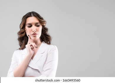 Portrait of beautiful cute young woman in a white dress  with pouted sensual lips and black shiny hair fink about new idea and looking at something