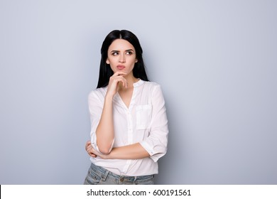 Portrait of beautiful cute young  woman with pouted sensual lips and black hair fink about new idea and looking at something