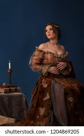 Portrait of beautiful dark haired woman dressed as a medieval historical character, posing in front of a dark blue background next to a table with books and a candle.