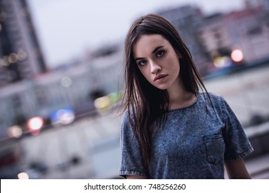 Portrait of beautiful dark-haired girl in jean dress looking at camera, on the city background
