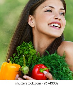 portrait of beautiful dark-haired smiling girl set with vegetables and herbs (eggplant, Bulgarian pepper red and yellow, dill and parsley) in hands on green background