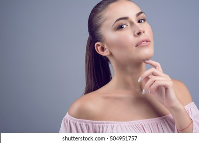 Portrait of beautiful dark-haired young model with perfect skin and wet nude make up on grey background. Her hand under the chin. Close up. Copy-space. Studio shot