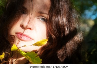 Portrait of a beautiful dark-haired young thoughtful seductive enigmatic woman in the forest in sunlight with green leaves
