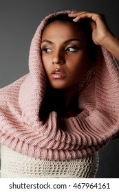 Portrait of beautiful dark-skinned girl with a knitted scarf on a grey background
