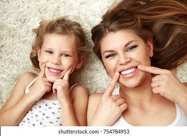 Portrait of beautiful daughter with mom showing their healthy white smile lying on carpet at home.