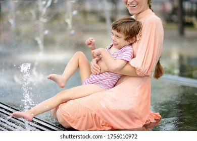 Portrait of beautiful disabled girl in the arms of his mother having fun in fountain of public park on sunny summer day. Child cerebral palsy. Disability. Inclusion. Family with disabled kid.