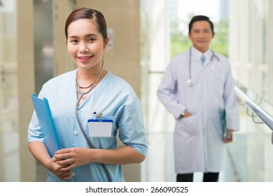 Portrait of beautiful doctor, he male colleague standing in the background