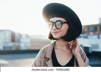Portrait of beautiful, dreamy and romantic young woman or teenager in hipster stylish fashion outfit, with artisan tattoos on arm, and nerdy glasses, looks to side at sunset over city
