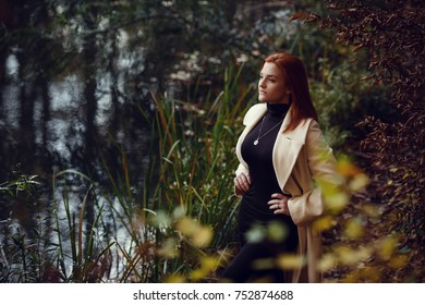 Portrait of a beautiful, dreamy and sad girl with red hair in white coat autumn.