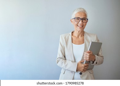 Portrait of a beautiful elderly business woman, smiling, isolated on grey background. Woman headshot looking at camera. Portrait of beautiful mature woman. Smiling senior woman.