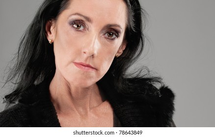 Portrait of beautiful elderly dark-haired woman in black clothes .