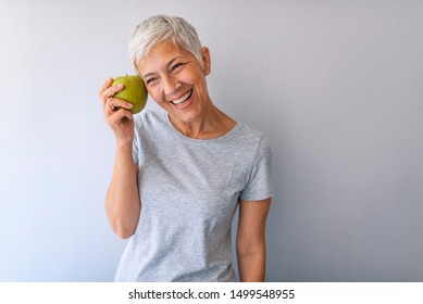 Portrait of a beautiful elderly woman holding an apple, smiling, isolated on gray background. Happy Woman Holding Granny Smith Apple. An aple a day keeps doctor away