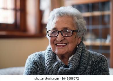 Portrait beautiful elderly woman smiling sitting on sofa at home enjoying retirement