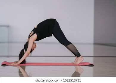Portrait of a beautiful, elegant and attractive Indian Asian woman doing a downward facing dog yoga pose on an exercise mat in the gym or at home during the morning.