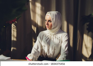 Portrait of a beautiful, elegant and attractive young Malay Asian Muslim woman in a dress and an hijab head scarf.