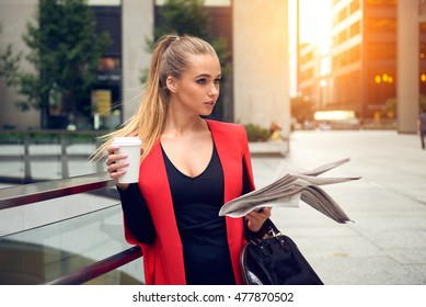 Portrait of beautiful elegant business woman walking to the city office with a coffee, newspaper and smiling outdoor