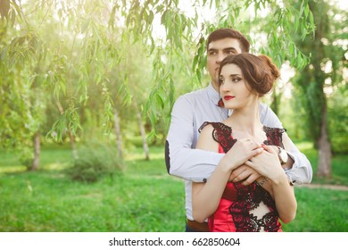 Portrait of a beautiful elegant couple in love, hugs in the park, romantic date. Stylish man and woman in red dress