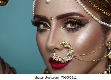 Portrait of a Beautiful Elegant Female Indian Model in Traditional Ethnic Asian Bridal Costume with Makeup and Heavy Jewellery in studio blue background