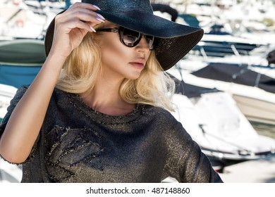 Portrait of the beautiful elegant luxury sexy blonde model wearing a hat and sunglasses which stands on a yacht in Cannes, France