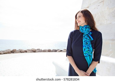 Portrait of beautiful elegant professional woman relaxing, looking away and smiling. Confident business woman wearing smart dress and scarf, outdoors. Healthy aspirational lifestyle, sunny exterior.