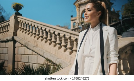 Portrait of beautiful elegant woman in classic white suit confidently looking away in old city park