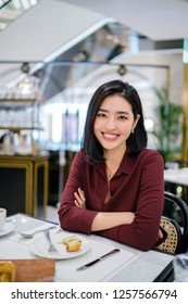 A portrait of a beautiful and elegant young Korean Asian woman sitting in a classy indoors cafe. She is smiling and wearing a silk maroon blouse.