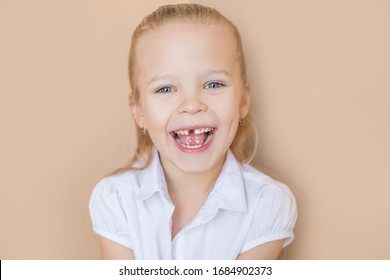 portrait of beautiful emotional baby girl  that lost first tooth