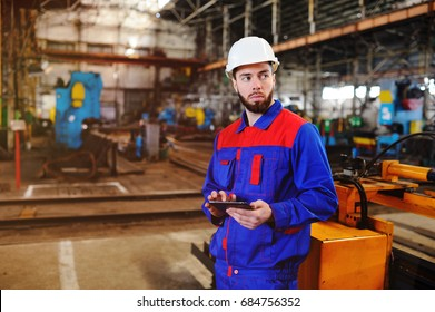 Portrait of a beautiful engineer in a construction helmet with a touch tablet on a factory background. male industrial technician working inside a factory