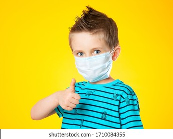Portrait of a beautiful European boy in a medical mask on a yellow background. The child shows the sign super, class. Big blue eye. Epidemics, pandemics, and the fight against coronovirus.
