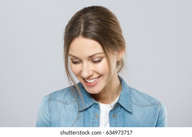 Portrait of beautiful European lady with simple hairstyle and light everyday makeup isolated on grey background turned leftwards and casting down her eyes, smiling timidly and showing coyness.