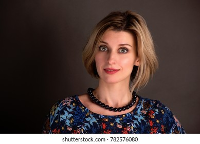 Portrait of beautiful excited blond woman with bob hairstyle wearing colorful dress on brown background
