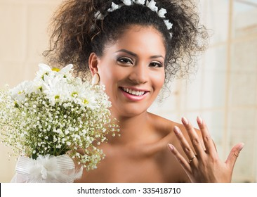 Portrait of beautiful exotic African American bride wearing white dress and holding flower bouquet showing wedding ring