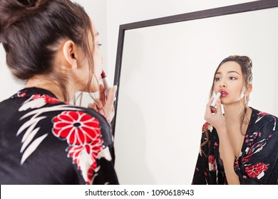Portrait of beautiful exotic model with flawless skin applying lipstick make up wearing robe, mirror reflection, grooming vanity indoors. Young woman using cosmetics, personal care lifestyle.