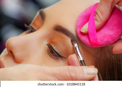 Portrait of beautiful face of young woman getting make-up. The artist is applying eyeshadow on her eyebrow using a brush. The lady closed eyes with relaxation, in a blurred background