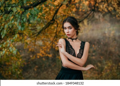Portrait of beautiful fairy girl in black dark dress standing next to colorful autumn tree bright orange leaves. Art work of romantic elegant medieval woman. Pretty tenderness model looks at camera