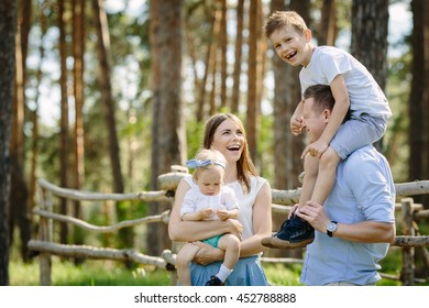 Portrait of beautiful family of four people mother father son daughter talking park near forest