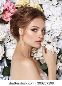 Portrait of a beautiful fashion bride, sweet and sensual. Wedding make up and hair. Flowers background. Art modern style. Blue eyes