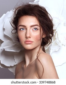 Portrait of a beautiful fashion brunette bride, sweet and sensual. Wedding make up and hair. Flowers background. Art modern style. Blue eyes.
