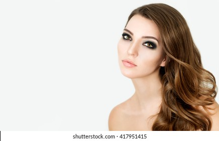 Portrait of Beautiful Fashion Model with Bright Eye Make up and Long Wavy Hair.  Perfect Fresh Skin and Long Eyelashes.  Make up and Hair. Lashes.
