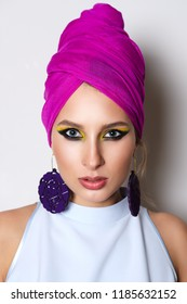 Portrait of beautiful fashion model in fitted dress and turban on head. Bright makeup and big earrings