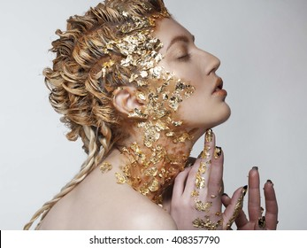 Portrait of beautiful fashion model with gold foil on face and hair