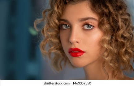 Portrait of Beautiful Fashion Model with Wavy Curly Hair and Colored Make-up with red Lips is posing front the Window. Make up and Hair. Haircare concept. Close-up, Selective focus.